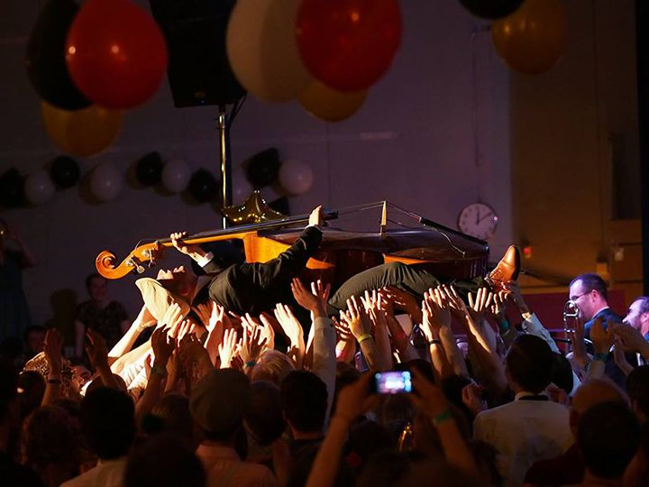 A double bass player crowd surfing