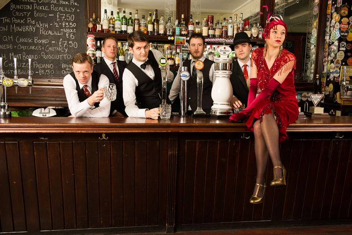 Band members dressed in vintage clothes behind a pub bar